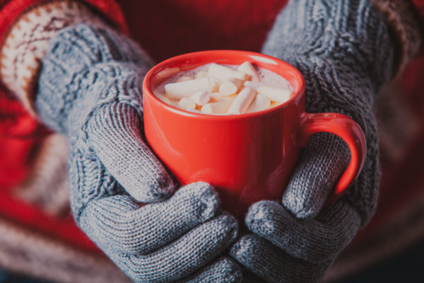Warm winter photo which hands in knitted gloves holding a mug cocoa with marshmallow